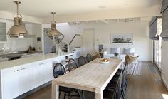 Beautiful kitchen with Ralph Lauren Home Montauk Pendants over long kitchen island with white quartz countertops.