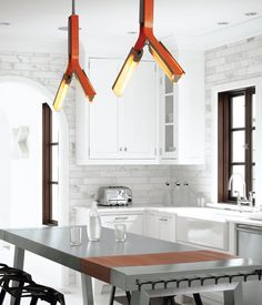 #kitchen Designer Barbara Hill had the overhead lighting in the kitchen customized by Rich Brilliant Willing in a pert orange that a...