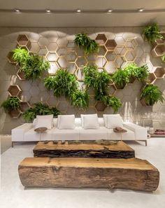 Living Garden – Sandra Moura e Leila Azzouz. Com pé direito elevado, as paredes ganham destaque. Uma delas recebe a instalação de hexágonos produzidos em laca fosca, madeira e estrutura de ferro pintada. Ela abriga um delicado jardim vertical.