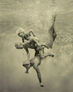 Delightful vintage underwater photo of a mother diving with her two children coming along for the ride.