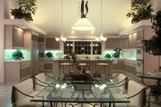 Custom kitchen with extensive use of glass; includes glass cabinets and glass dining table. Workspace is backlit with cool blue lighting
