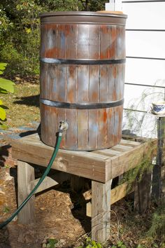 A little house in the suburbs plastic rain barrel painted to look like a wooden rain barrel.