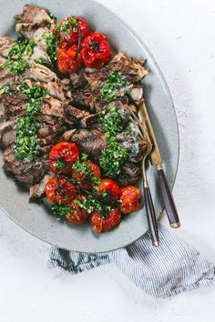 Delicious RIBEYE STEAK IN THE OVEN served with a chimichurri sauce, compound butter and roasted tomatoes. Get the recipe on lenaskitchenblog.com