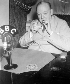 Winston Churchill lights a cigar in a BBC radio studio in 1943