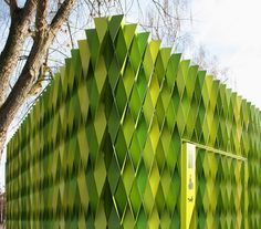 Public prefab restroom in Uster (CH), architects Gramazio & Kohler slapped 295 bright green, laser-cut, folded aluminum strips.