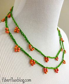 This sweet and simple necklace celebrates beautiful flowers growing on a vine. Crocheted in leaf green and accented with coral glass beads, this is an easy project to get yourself crocheting with embroidery floss!
