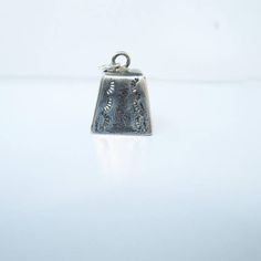 A vintage Native American sterling silver cowbell charm with stampwork on all sides. It measures 3/4 with jump ring. Has a clapper inside so it does give off a tinkling noise. It weighs 2.05 grams. not marked, but tests positive for sterling.