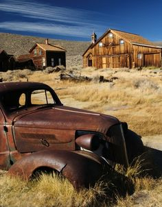 "old weathered barns, old tiny log cabins, and junker cars, otherwise known as ""Montana Yard Art"".....So sad...this was someone's home; what happened that caused it all just to be left."