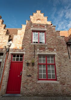Beautiful Belgian gabled house in Bruges, with red door and windows, and mixed, multicolor bricks #belgium