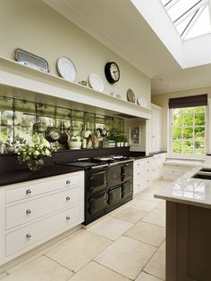 This gorgeous Martin Moore, martinmoore.com, kitchen is in an extension in London and features a striking metallic splashback and jet black range cooker.