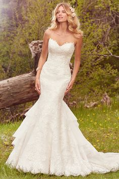 This glamorous fit-and-flare features a layer of lace motifs atop crosshatched tulle, complete with a gorgeous layered train and strapless sweetheart neckline. Finished with crystal buttons over zipper and inner corset closure. Goldie from @maggiesottero on @weddingwire.