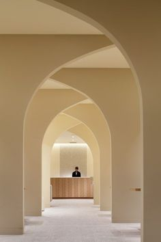 """Modern archways created by overlapping """"half arches"""" lead to a classic herringbone counter at the Hotel Nikko Kumamoto Bridal Salon, designed by Ryo Matsui Architects Inc. #ARCHitecture"""
