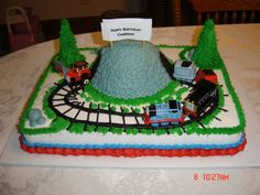 thomas the train cake, chocolate cake with buttercream icing, wonder mold for the mountain covered in buttercream also, trees are sugar cones.