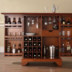 Expandable bar cabinet with a sixteen-bottle wine rack and hand-rubbed cherry finish. Doors open to glassware storage and a drawer. Produ...
