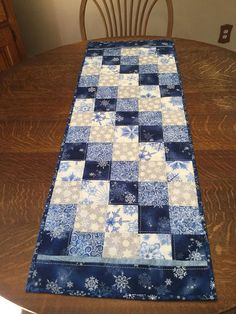 This is the perfect table runner for your decorating right through the Winter season. If you like to decorate for the Holiday season with colors other than red and green, this runner is a perfect choice. Quilted table runner measuring 43x15, created in a diagonal block pattern of