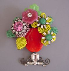 """VRBA basket brooch, red glass body with green pressed glass and yellow glass seed bead leaves and flowers, pink and clear rhinestone flower and pink pressed glass flower and, 4"""" by 3-1/2""""."""