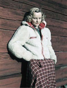 Klädd för friluftsliv. Blond kvinna i vit fuskpälsjacka och rutig kjol vid rödmålad timmervägg. 1941. Foto. Gunnar Lundh. CC-BY.