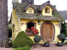 Isn't this shed adorable? The curved door, different dormer sizes, and window shapes are quite unique.