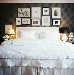 white linens/headboard against dark wallpaper, with various photos/art