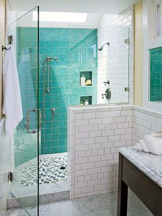 Situate a shower seat across from at least one showerhead so you can laze in the spray. This walk-in shower design places a small built-in seat in a corner opposite the main showerhead and next to a handheld spray. Green tiles meld the custom-fitted seat with the shower's shimmering walls./