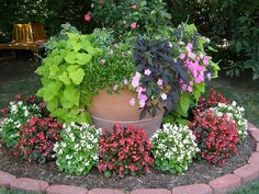 Circular Garden Bed Idea.  I would use more permanent and edible plants for the perimeter and flowers in the center planter.