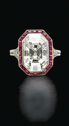 AN ART DECO DIAMOND AND RUBY RING Set with an octagonal-shaped diamond, within a calibré-cut ruby surround, mounted in platinum, circa 1930.