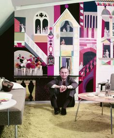 Alexander Girard in front of his tissue paper mural in the Herman Miller showroom.  EAMES COFFEE TABLE on the right, Nelson sofa on the left, both by #hermanmiller