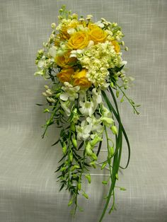 Cascading bridal bouquet including white dendrobium orchids, butter yellow stock, high and exotic roses, white spray roses and white feverfew