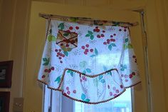 apron curtain....I have my mom's antique aprons hanging in my kitchen for curtains... mine are hung differently...