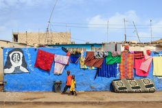 Children walking in the streets of Saint-Louis, Senegal. The city has many blue walls with religious paintings and you can see the colorful laundry all around by Gil Kreslavsky