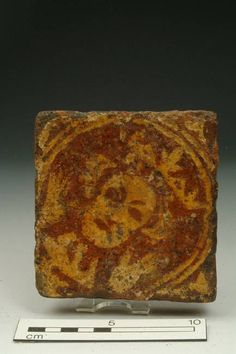 tile; floor tile Accession number: 6847 Production date: Medieval; 13th-14th century Material: ceramic; earthenware Measurements: L 116 mm; W 111 mm; T 24 mm Museum Section: Medieval Summary: Floor tile with design of face in yellow within a circle on red fabric.
