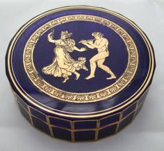 A RARE MOSER OROPLASTIC DECORATION BOX This is a rare example of the 'oroplastic' acid cut-back technique patented by Moser in 1919 and used here on a lidded blue glass box. The oroplastic design was typically used as a frieze round the rim or foot of a vase and heightened with pure or polychromatic gilding but this example differs as it has a large figural medallion in the centre of the box lid and further hand gilding on the edges of each facet. C1920
