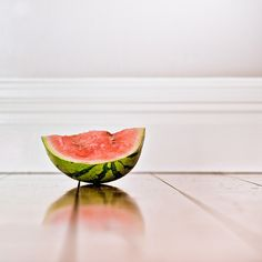https://flic.kr/p/7G34Tb | Minimalist Fruit Photography | Minimalist Fruit Photography: Lightroom really saved this image and helped me selectively pull out the watermellon texture and color. It really does look delicious. I desaturated the wood floor and enhanced the reflection. I thought this was a very interesting comparison to the Snip Snip image shown to the right of this one, both of these were taken in the same light. Definitely shows how much processing can change your final image…