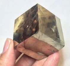 Lovers of beauty and symmetry: this crystal is for you! XL Iron Pyrite cubic crystal from Spain. This large substantial  specimen is uncut and unpolished; it has some clean and some rougher edges preserving its natural beauty. (The cubic shape results from orderly packing at the atomic level and repeats itself throughout the lattice.) The larger cube also includes tiny edges of smaller twins including a twin that appears to slice through the host crystal. Equally stunning for its symmetry as…
