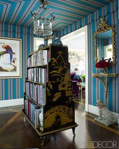 alex papachristidis:  the walls and ceiling of the entrance hall are sheathed in a lee jofa linen, the print is by walton ford, and the tole light fixture is vintage; the bookcase is antique and the mirror is italian.