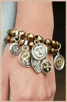 Waxing Poetic bracelet- Left to right: Butterfly Whimsies charm, Faith camp charm, Personalized Rivet charm, Personalized Round Insignia charm, Dome Seals Croix charm, Sacred Heart sterling silver pendant, Wing & A Prayer Crown charm, each attached with Silver charm clip on two layered large Brass Ball bracelets.