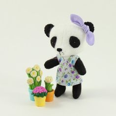 This tiny wool blend felt Panda is styled in a cute little dress and knotted bow made of 100% cotton. She is about 3 inches tall and her tiny hands