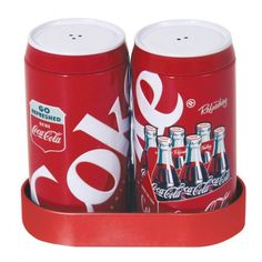 Shake up some fun during your next meal ! This charming salt and pepper duo are made from steel and feature bright red Coca - Cola classic designs . Comes with a tray they nestle into when not in use