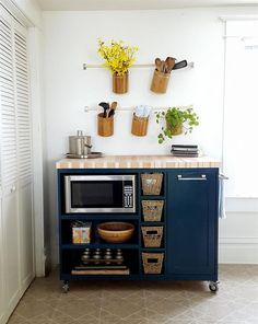 This rolling kitchen island features a beautiful butcher-block top, a place to store your microwave, and flip-out trash can storage.