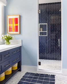 Navy Blue Herringbone Shower Wall Tile Navy Blue Vanity with Basket Storage Light Blue Walls in the Bathroom Glass Frameless Shower Door Navy Blue Bathrooms, Navy Bathroom, Bathroom Cost, Neutral Bathroom, Transitional Bathroom, Blue Vanity, Small Shower Remodel, Light Blue Walls, Navy Blue Walls
