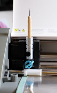 Adding a stylus to the Chomas Creations adjustable pen holder for the Silhouette Cameo to emboss on a metal sheet on an embossing mat.