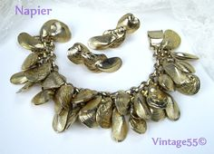 Vintage Bracelet Napier Charm Sea Shells Gold tone clip Earrings. $92.00, via Etsy.