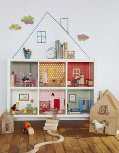 A doll house made out of storage cubes... I love the wire/string roof and chimney on the wall, this is such a cute idea.