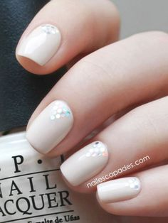 Simple and pretty, this chic manicure strategically placeshexagon glitterin a tiny triangle that'stotally eye-catching. Click through to see more and for more ways to upgrade a nude manicure.