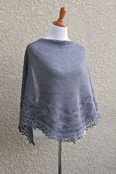 This hand knit shawl is made of 100% wool in lovely grey color. The shawl is half-circle shape and perfectly wide to wrap around the body. Laced edge adds feminine look to simple and elegant body. It