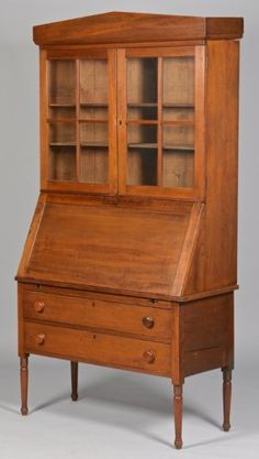"Southern desk and bookcase, 2 piece construction, cherry and walnut with poplar wood, attributed to Alabama, pediment style cornice over two glazed doors, each divided into four panes of glass, over a slant front desk section with fitted interior including cubbyholes and two small drawers. Two long dovetailed drawers with wood knobs, and four slightly tapering turned legs with ring turnings at top. 78"" H x 41 3/4"" W x 18 1/4"" D."