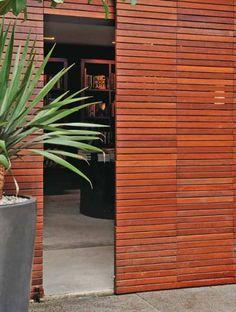 """De correr - O arquiteto Ricardo Caminada usou placas de deck de maçaranduba (50 x 50 cm, da Tora Brasil), fixadas numa estrutura metálica (Alumart) para compor a porta de correr de 3 x 2,50 m. """"Ficou tão leve que não requer puxador"""", diz Ricardo."""