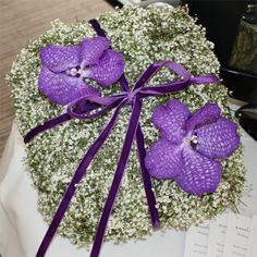 alternative ring pillow. baby's breath wrapped in silver wire, a purple ribbon and 2 Vanda orchids