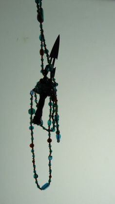 Knife dangling from a string of glass beads