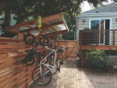 Covered hanging bike rack (Built with Tight Knot Cedar) Garden Bike Storage, Bicycle Storage Rack, Bicycle Rack, Storage Racks, Bicycle Tools, Wall Storage, Hanging Bike Rack, Outdoor Bike Storage, Vertical Bike Rack